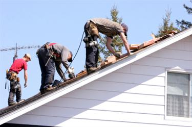 Roof installation on a home. Roofers laying shingles on roof.